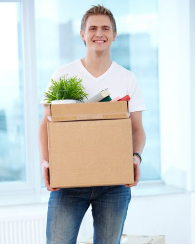 A young guy with boxes looking at camera in new flat